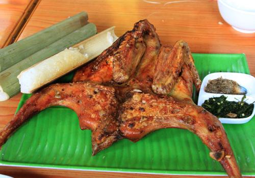 Gà rừng nướng khu du lịch thác đa, con gà rừng nướng, 1 bát chấm gia vị, 3 khúc cơm tre trên chiếc đĩa sứ màu xanh đặt ở trên bàn gỗ màu nâu