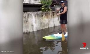 Khách du lịch chèo ván lướt sóng trên đường phố ngập lũ ở Bali